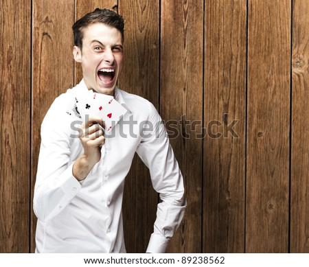 portrait of young man shouting with megaphone against a wooden wall man holding poker cards against a wooden wall - stock photo