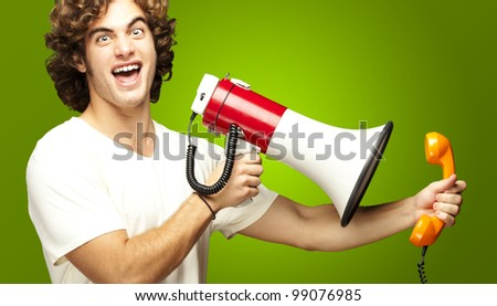 portrait of young man shouting with megaphone and talking on vintage telephone over green - stock photo