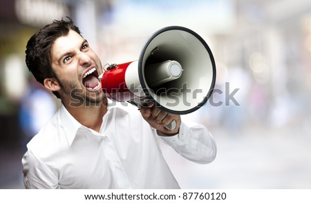 portrait of young man shouting with megaphone at crowded place - stock photo