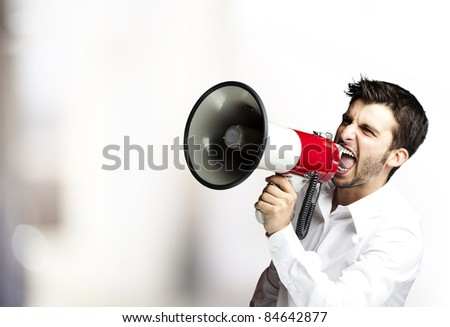 portrait of young man shouting with megaphone indoor - stock photo