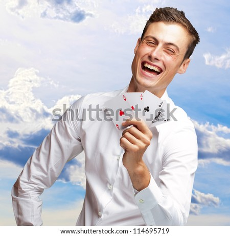 Portrait Of Young Man Showing Poker Cards, Outdoor - stock photo