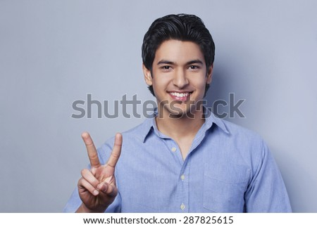 Portrait of young man showing V-sign - stock photo