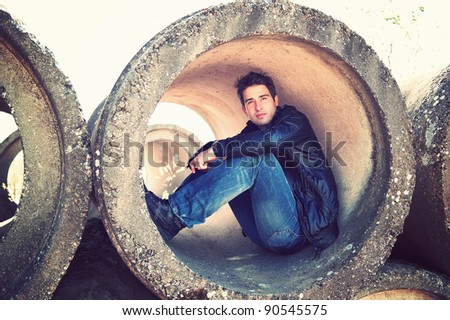 portrait of young man sitting in concrete tube - stock photo