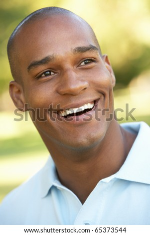 Portrait Of Young Man Sitting In Park - stock photo