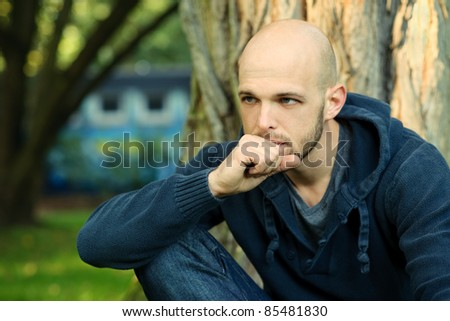 Portrait of young man sitting in park and thinking