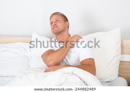 Portrait Of Young Man Sitting On Bed Suffering From Shoulder Pain - stock photo