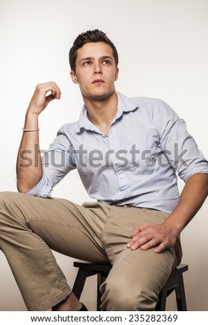 Portrait of young man sitting on chair - stock photo