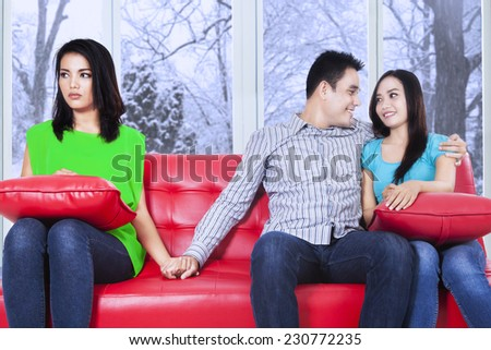 Portrait of young man sitting on sofa and embrace his girlfriend while holding hands with his friend - stock photo