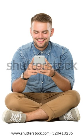 portrait of young  man sitting on the floor using a cellphone, isolated. ready for your design - stock photo