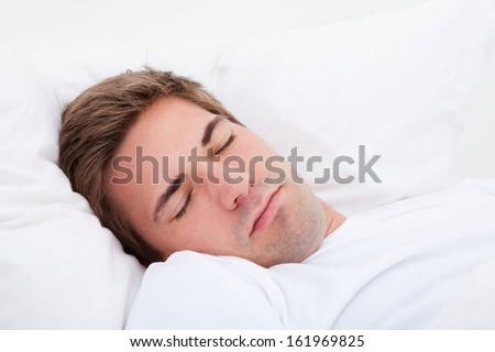 Portrait Of Young Man Sleeping In Bed - stock photo