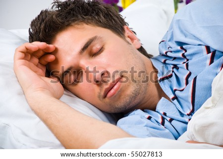 Portrait of young man sleeping in his bed