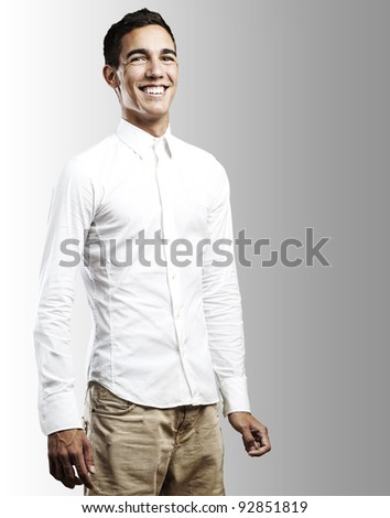 portrait of young man smiling against a grey background - stock photo