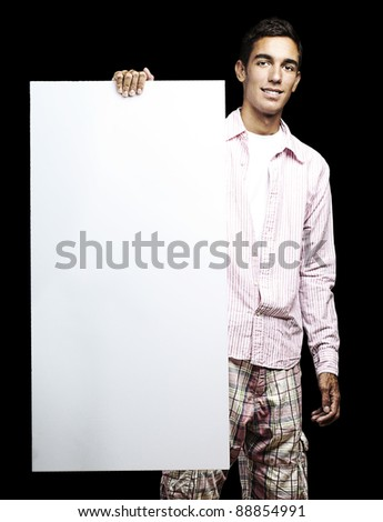 portrait of young man smiling and holding a poster on black background - stock photo