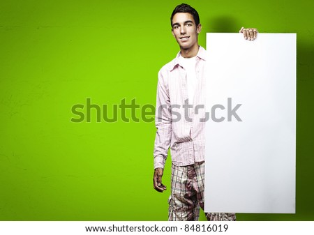 portrait of young man smiling and holding a poster on green background - stock photo