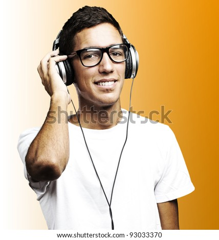 portrait of young man smiling and listening to music against a blue background