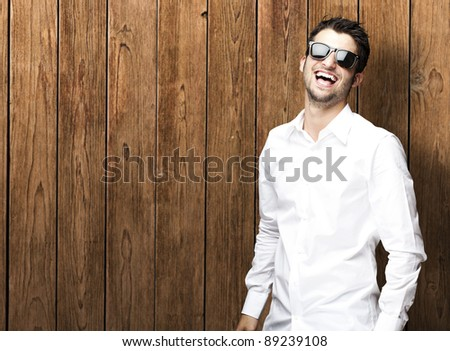 portrait of young man smiling wearing sunglasses against a wooden wall - stock photo