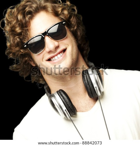 portrait of young man smiling with headphones over black background
