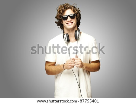 portrait of young man smiling with headphones over grey background