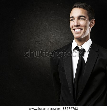 portrait of young man smiling with suit against a grunge background - stock photo