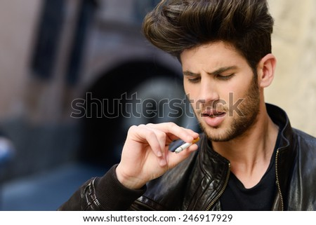 Portrait of young man smoking a cigarette in urban background - stock photo