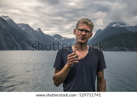 Portrait of young man smoking, close-up, Norway