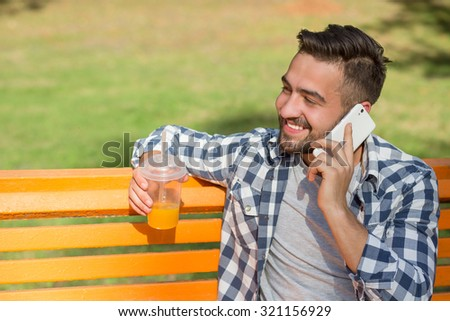 Portrait of young man speaking over mobile phone and drinking orange cocktail. Short-haired man looking away while sitting on the bench in the park. - stock photo