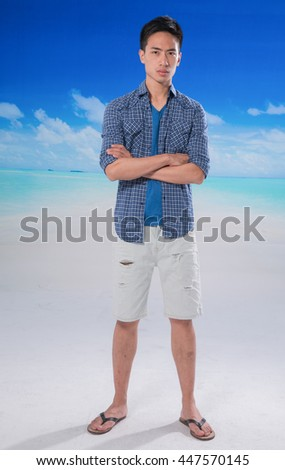 portrait of young man standing at beach background - stock photo