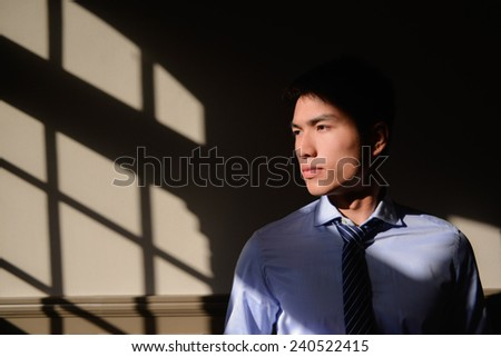 Portrait of young man standing in the interior of coffee shop