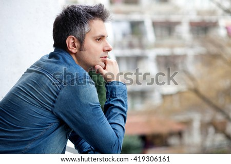Portrait of young man standing on balcony - stock photo