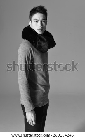 portrait of young man standing with hands in pockets - stock photo