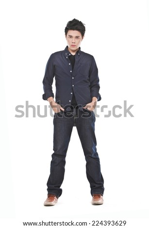portrait of young man standing with hands in pockets over white background