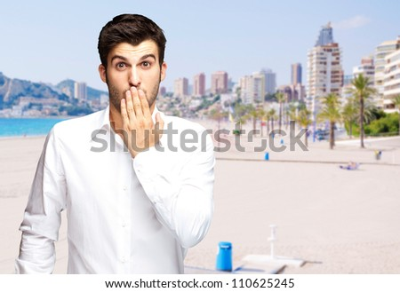 portrait of young man surprised against a beach - stock photo