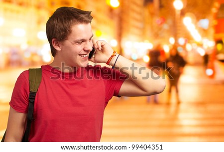 portrait of young man talking on mobile at night city - stock photo