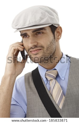 Portrait of young man talking on mobilephone, smiling, looking away, wearing hat. - stock photo