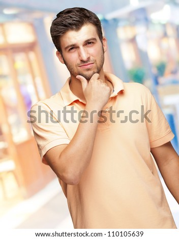 Portrait Of Young Man Touching His Chin, indoor - stock photo