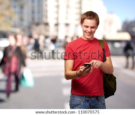 portrait of young man touching mobile screen at crowded street - stock photo