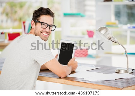 Portrait of young man using digital tablet at his desk in the office - stock photo
