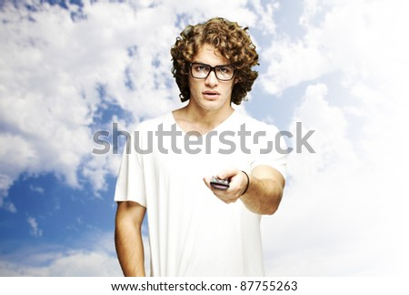 portrait of young man using tv control against a cloudy sky background - stock photo