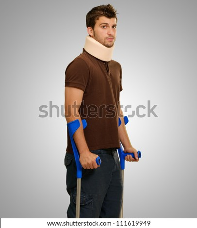 Portrait Of Young Man Walking On Crutches On Gray Background - stock photo