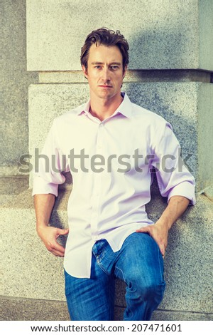 Portrait of Young Man. Wearing a light pink shirt, blue jeans, bending a leg, a young handsome guy is standing against a concrete wall, confidently looking at you.  - stock photo