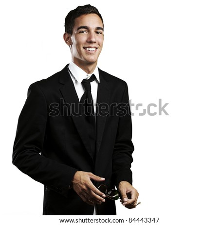 portrait of young man wearing a suit and holding a sunglasses against a white background