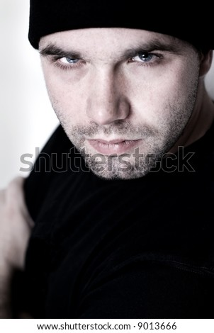 Portrait of young man wearing beanie - selective focus on the model's right eye. - stock photo