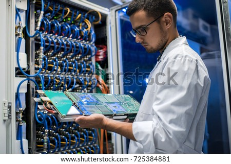 Portrait of young man wearing lab coat holding blade server and looking at it while working with supercomputer