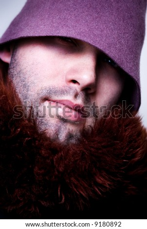 Portrait of young man wearing purple hat and fur, sparkle in the eye, eyes in shadow. - stock photo