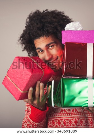 Portrait of young man with afro holding a Christmas gifts - stock photo