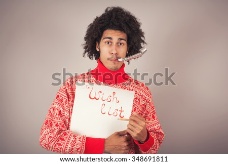 Portrait of young man with afro preparing Christmas letter or wish list - stock photo