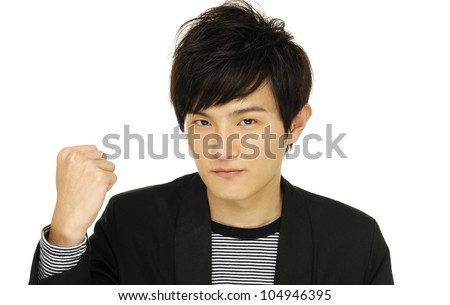 Portrait of young man with arm and fist raised up - stock photo
