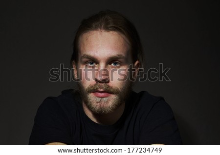 portrait of young man with beard and mustache on dark background - stock photo