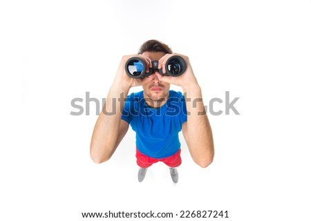 portrait of young man with binoculars over white background. top view of young man looking through binoculars up - stock photo