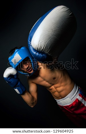 Portrait of young man with boxing helmet and gloves over black background - stock photo